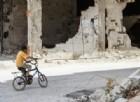 Un bimbo siriano si aggira in bicicletta tra le rovine di Homs.