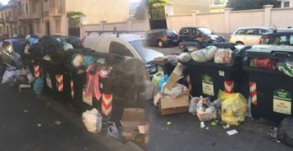 I bidoni di immondizia stracolmi: il pattume invade la strada