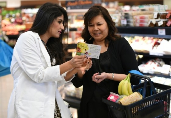 Doctor's assitant Marina Sarwary (L) speaks with a shoper about organic food choices as part of the «Shop with a Doc» program at a supermarket in Irvine, California