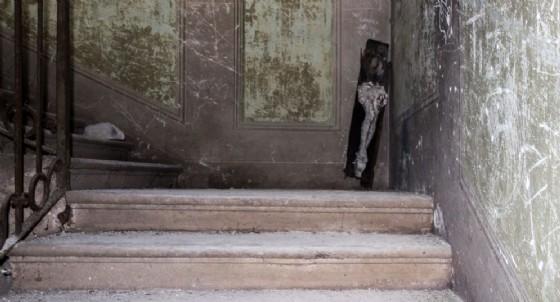 Un crocifisso spezzato in una casa abbandonata (© Adobe Stock)