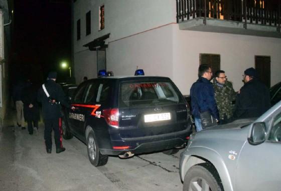 Carabinieri in divisa ed in borghese davanti l'ingresso dell'abitazione
