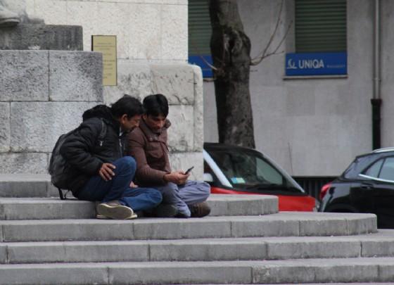 Migranti a caccia di wi-fi in piazzale XXVI Luglio (© Diario di Udine)