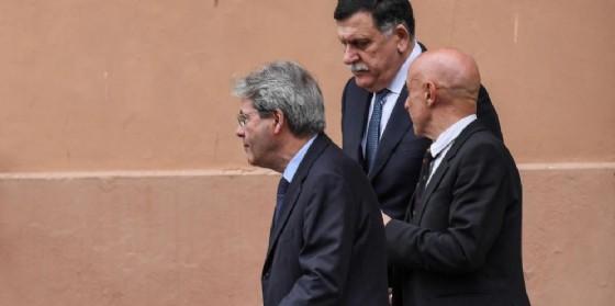 Il premier italiano Paolo Gentiloni, il ministro dell'Interno Marco Minniti e il primo ministro libico Fayez al-Serraj al vertice Ue-Africa.