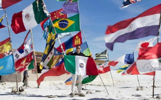Marco Concina con una bandiera che rappresenta la sua terra (Corno di Rosazzo e Campolongo al Torre) nel deserto del sale dello Uyuni (© Marco Concina)