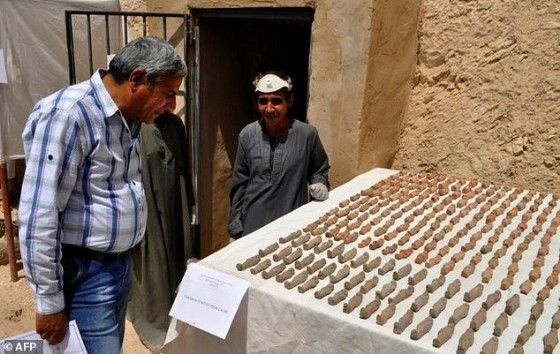A member (R) of an Egyptian archaeological team stands near artifacts discovered in a 3,500-year-old tomb in the Draa Abul Nagaa necropolis, near the southern city of Luxor, on April 18, 2017