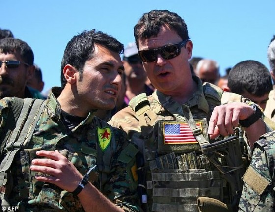 A US officer speaks with a fighter from the Kurdish People's Protection Units (YPG) at the site of Turkish air strikes in northeastern Syria on April 25, 2017