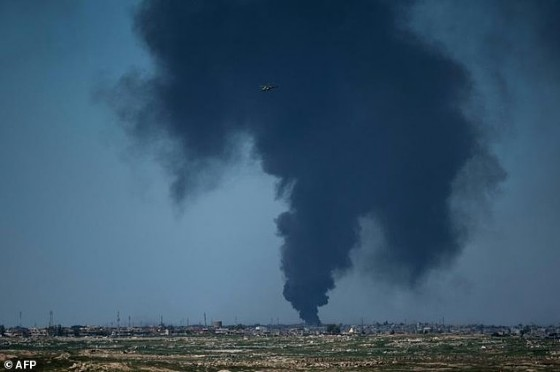An Iraqi forces helicopter flies in front of black smoke rising from the horizon in west Mosul on April 25, 2017