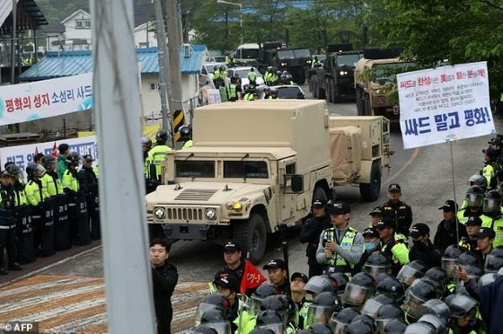 Protesters and police stand by as trailers carrying US THAAD missile defence equipment enter a deployment site in Seongju, South Korea, on April 26, 2017