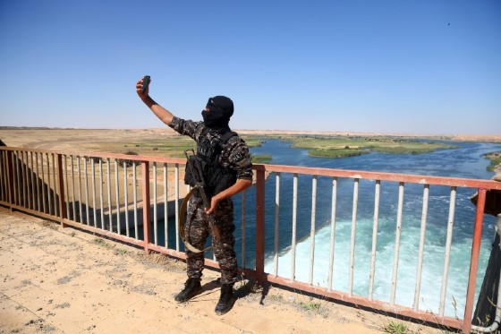 A member of the Special forces from the US-backed Syrian Democratic Forces (SDF) takes a picture at the Tabqa dam, on May 12, 2017, after it was recaptured from Islamic State group fighters