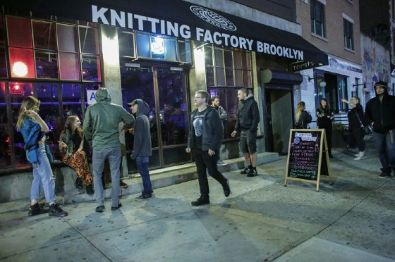 People walk past a sign for a Lights Out concert at The Knitting Factory in Brooklyn New York on May 12, 2017