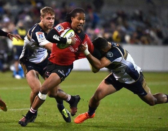Lions' Sylvian Mahuza (C) is tackled by Brumbies' Wharenui Hawera (R) and Kyle Godwin during their Super Rugby match, in Canberra, on May 12, 2017