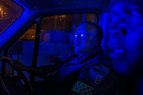 Paramedics Patricia September and Simphiwe Ngavu are bathed in the blue light of the South African Police Services van sticking close to them as they attend to a call in the crime-ridden Cape Town township of Nyanga