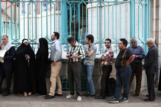 Iranians wait in a queue for the opening of a polling station in presidential elections in Tehran on May 19, 2017