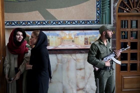 Iranians queue to vote in presidential elections as a soldier stands guard at a polling station in Tehran on May 19, 2017