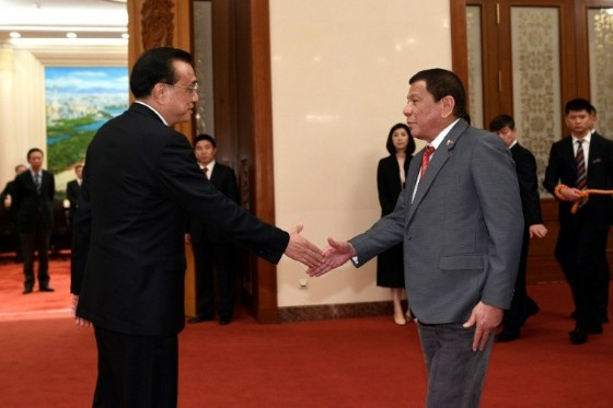 Chinese Premier Li Keqiang (L) shakes hands with Philippine President Rodrigo Duterte before a meeting at the Great Hall of the People in Beijing