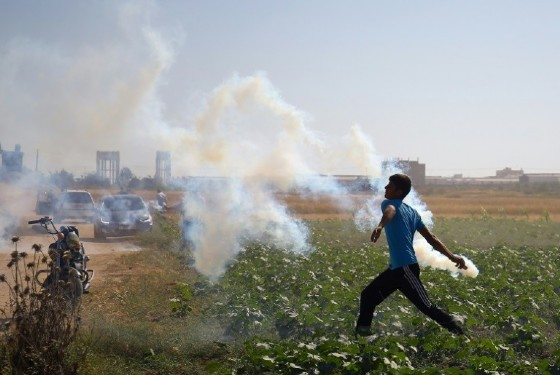 A Palestinian protester hurls a teargas canister back at Israeli soldiers during clashes near the border fence east of Gaza City on May 19, 2017
