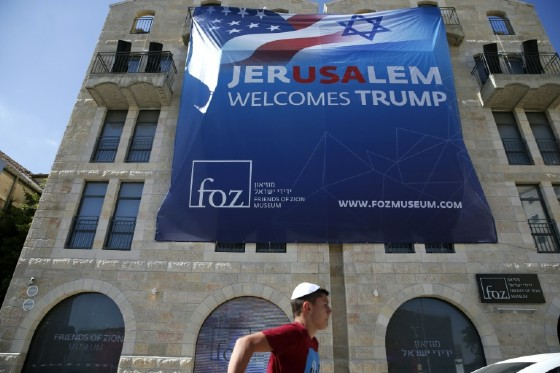 An Israeli youth walks past a poster welcoming and supporting US President Donald Trump in downtown Jerusalem