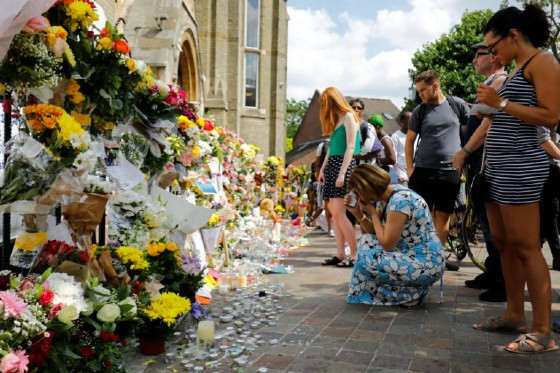 People look at floral tributes for victims of the Grenfell Tower block fire that have been left outside the Notting Hill Methodist Church in west London, on June 17, 2017