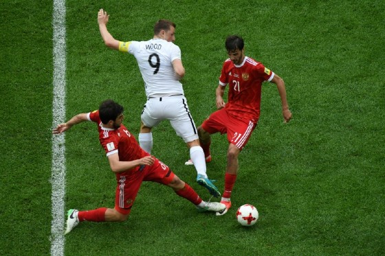 New Zealand's forward Chris Wood (C) is tackled by Russia's defender Georgiy Dzhikiya (L) and Russia's midfielder Alexander Erokhin (R) during the 2017 Confederations Cup group A football match June 17, 2017