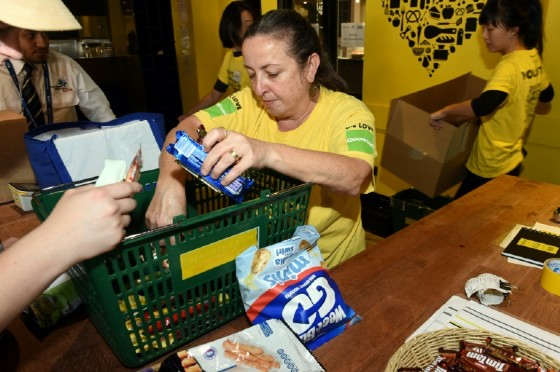 A volunteer removes items from a basket at OzHarvest Market, a recycled food supermarket, which takes surplus products normally thrown out by major retailers, airlines and other suppliers, and gives them away for free