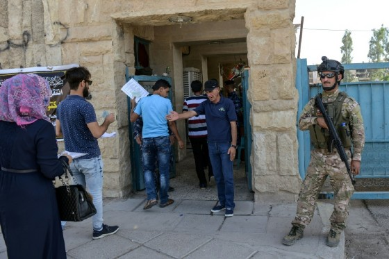 Iraqi students are searched outside the University of Mosul as they arrive to take their exams