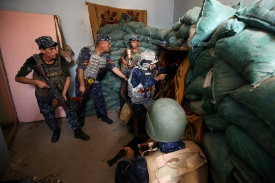 Iraqi forces take positions inside a building as they advance towards Mosul's Old City on June 18, 2017