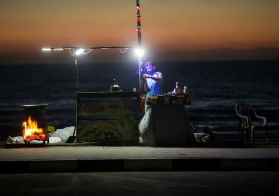 This file photo taken on June 11, 2017 shows a Palestinian street vendor standing behind his stall in front of the beach in Gaza City during a power outage