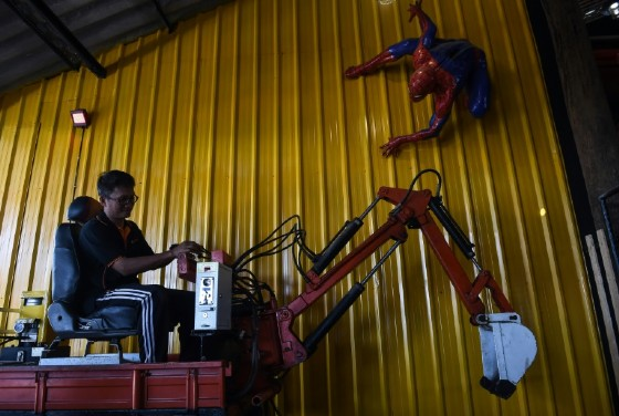 Artist Pairoj Thanomwong operating mechanical toys at Ban Hun Lek, a metalworks shop renowned for giant statues of Transformers, The Hulk and other pop icons