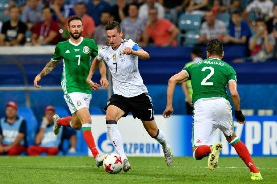 Germany's midfielder Julian Draxler (C) fights for the ball with Mexico's midfielder Miguel Layun (L) and Mexico's defender Nestor Araujo during the 2017 Confederations Cup semi-final football match June 29, 2017