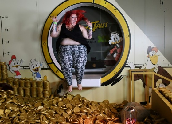 A woman jumps into the money pit at the Duck Tales exhibit at the D23 expo