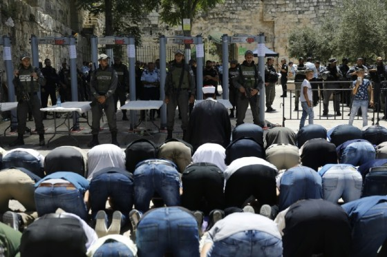 Israeli border policemen stand watch as Muslim worshippers pray outside an entrance to the Al-Aqsa mosque compound on July 16, 2017 in protest at new security measures including metal detectors and cameras