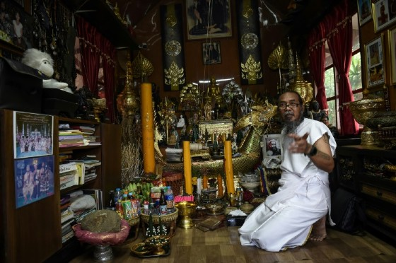 Surrounded by a cornucopia of glittering Buddha statues, eerie dolls and other spiritual trinkets, the 57-year-old Thai 'hermit' Toon uses powders and ointments to conduct his 'good luck' ritual.