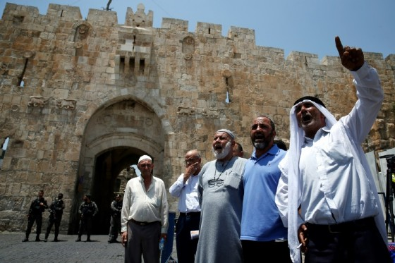 Palestinians chant slogans outside the Lions Gate, a main entrance to the Al-Aqsa mosque compound, due to newly implemented security measures by Israeli authorities, in Jerusalem's Old City on July 17, 2017