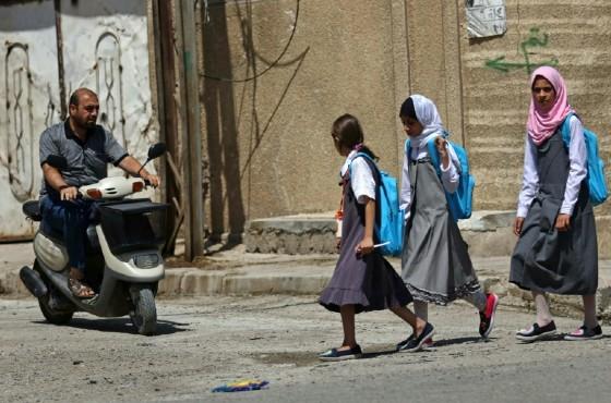 Iraqi girls walk to school in western Mosul on July 27, 2017