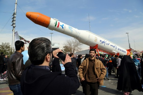 Iranians take pictures of the Simorgh satellite rocket during celebrations in Tehran to mark the 37th anniversary of the Islamic revolution on February 11, 2016