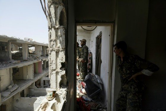 Members of the Syrian Democratic Forces, a US-backed Kurdish-Arab alliance, move through destroyed buildings in Raqa on July 28, 2017, as they battle jihadists in the city