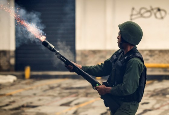 A member of the national guard fires a tear gas grenade during opposition-led clashes in Caracas on July 28