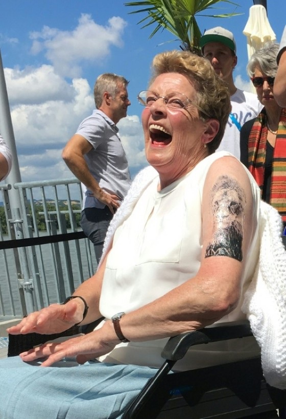 Maves Williams, grandmother of Great Britain's swimmer Adam Peaty, shows off her temporary tattoo, just like his grandson's, during the swimming competition at the 2017 FINA World Championships in Budapest