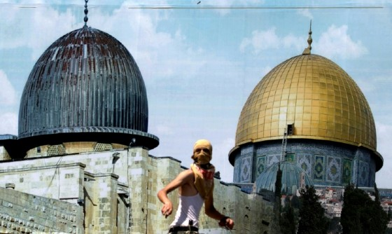A Palestinian protester stands in front of a mural depicting Jerusalem's golden-topped Dome of the Rock during clashes with Israeli security forces outside the West Bank city of Nablus on July 28, 2017