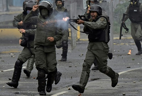 A member of the national guard fires his shotgun at opposition demonstrators during clashes in Caracas on July 28, 2017
