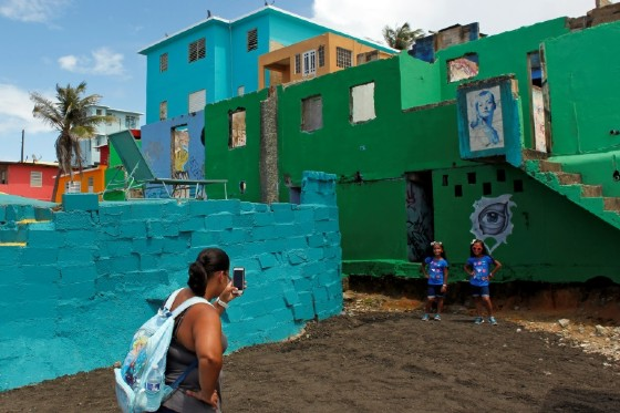 A woman takes photos in the Puerta Rican neighbourhood of La Perla