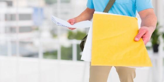 Un postino nell'atto della consegna (© Shutterstock.com)