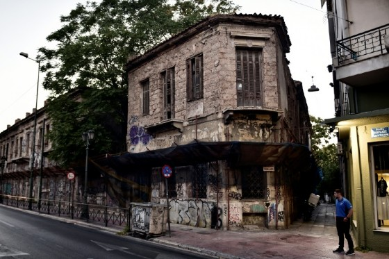 A man stands near the abandoned neoclassical former Hatzikostas Orphanage in Athens