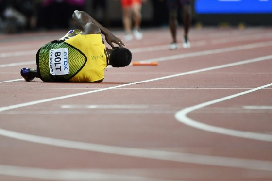 Jamaica's Usain Bolt goes down after pulling up injured in the final of the men's 4x100m relay athletics event at the 2017 IAAF World Championships at the London Stadium in London on August 12, 2017