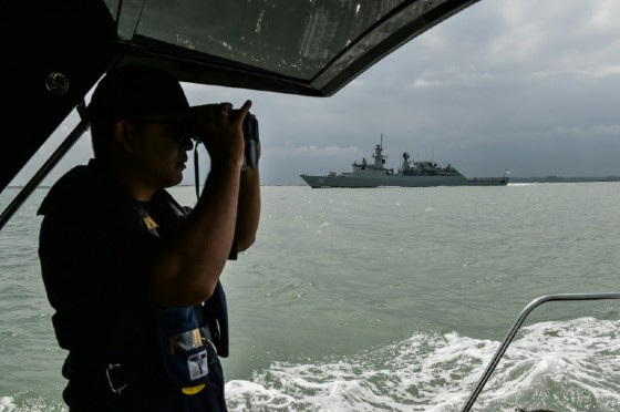 A member of the Malaysian Maritime Enforcement Agency officer scans the sea as part of the search and rescue effort