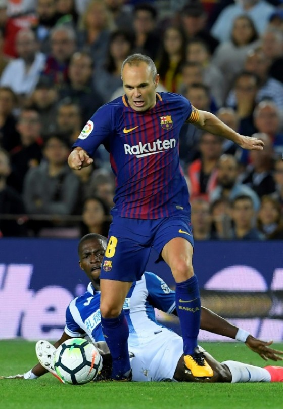 Barcelona's Andres Iniesta (up) fights for the ball with Espanyol's Papakouli Diop during their Spanish La Liga match, at the Camp Nou stadium in Barcelona, on September 9, 2017