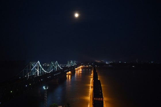 The North Korean town of Sinuiju, behind the Friendship Bridge (L) which connects Sinuiju and the the Chinese border city of Dandong