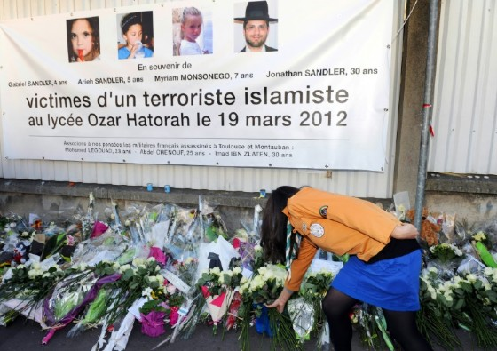 A bunch of white roses is laid on March 25, 2012 in Toulouse under a banner paying tribute to victims of jihadist Mohamed Merah who killed three children and a teacher at a Jewish school. The trial of his brother Abdelkader Merah begins October 2
