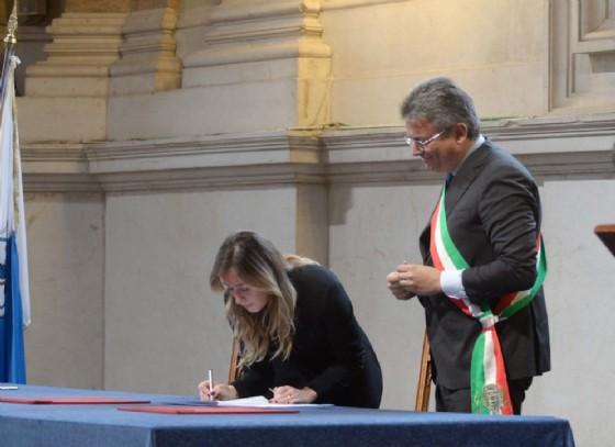 La firma del ministro Maria Elena Boschi sotto lo sguardo del sindaco Cavicchioli (foto Marco Ortogni)