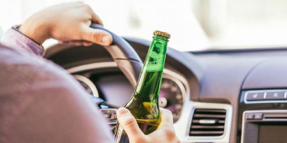 Un uomo alla guida con una birra